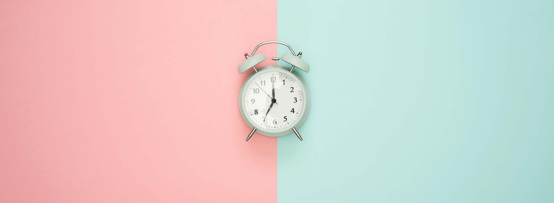 Analogue alarm clock on a pink and turquoise background
